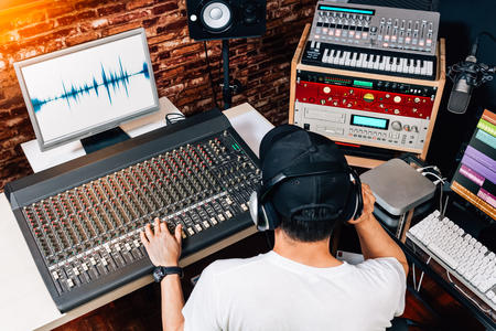 Photo pour asian male music producer, sound engineer, composer, dj working in studio. recording, broadcasting, audio video editing concept - image libre de droit