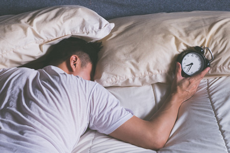 Photo pour sleeping asian young male disturbed by alarm clock early morning in bed - image libre de droit