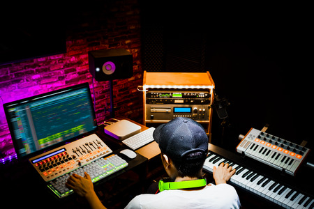 Photo for back of male asian producer working in sound design studio. music, film score, advertising footage digital editing, jingle song, voice actor recording, post production - Royalty Free Image
