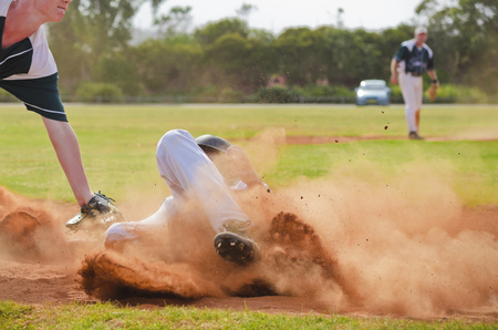 Photo for Adult baseball player sliding into third base - Royalty Free Image