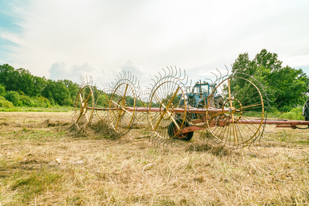 Photo for Tedders for hay in the meadow in the background of the forest - Royalty Free Image