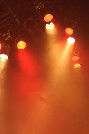 Bright spotlights shining down on to an empty stage creating a deep orange red misty or smokey glow