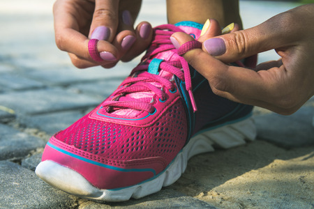 Hands of a young woman lacing bright pink and blue sneakers. Shoes standing on the pavement of stones and sand. In female hands purpleyellow manicure. Photographed closeup.