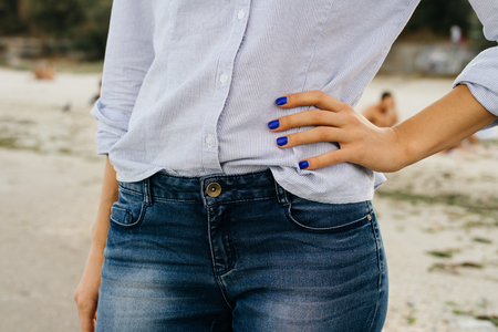 Foto de Details of women's clothing. The woman in jeans and shirt standing on the beach. Close-up, outdoors. - Imagen libre de derechos