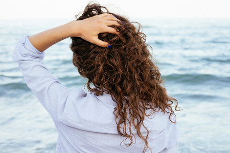 Photo pour Young woman in shirt looking at the sea and keeps her hair. Back view close-up. - image libre de droit
