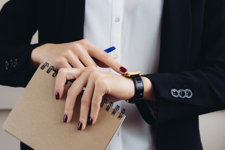 Foto de Woman in a business suit and dark red manicure holding a notebook and looks at his watch close-up - Imagen libre de derechos