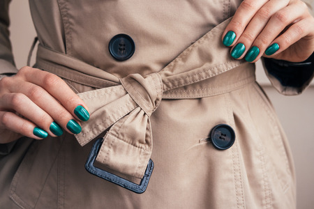 Photo for Female hands with a bright manicure tie belt on a coat, close-up - Royalty Free Image