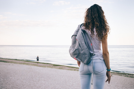 Foto de Young sporty woman with curly hair, wearing jeans and a backpack standing on the beach and looking at sea, view from the back - Imagen libre de derechos