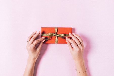 Foto de Top view of female hands tying a bow on a box with a gift on a pink background - Imagen libre de derechos
