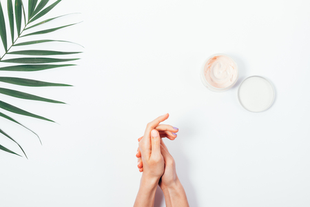 Photo pour Woman rubbing cream into the skin of hands on a white background top view - image libre de droit