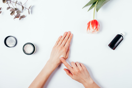 Photo pour Woman's hands apply cream on skin. The concept of pre-testing cosmetics before use. Top view of female hands among the feminine environment: tulip flower, eucalyptus branch, lotion and cream. Flat lay composition on white background. - image libre de droit