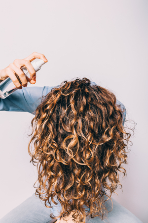 Foto de Head of young woman with long curly hair is lowered down to apply cosmetic care product. Female using spray with sea salt to make beachy waves hairstyle. - Imagen libre de derechos