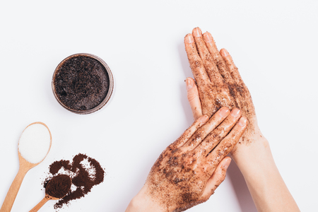 Foto de Female's hands apply massaging moves cosmetic scrub of ground coffee, sugar and coconut oil, top view on white table. - Imagen libre de derechos