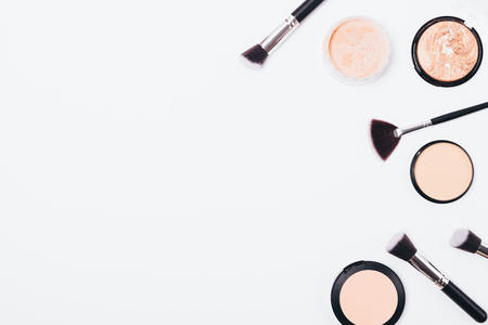 Foto de Flat lay frame of cosmetic powders and brushes on white background with copy space. Top view dry makeup products for even complexion and bronze tan. - Imagen libre de derechos