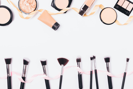 Foto de Make-up background of cosmetics for even complexion and professional brushes, top view. Flat lay frame of beauty products and accessories on white table with empty space in middle. - Imagen libre de derechos