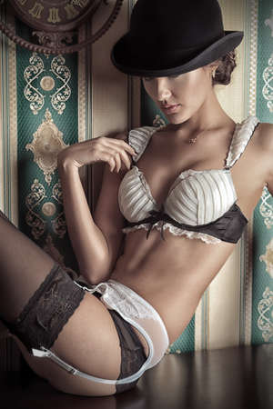 Portrait of beautiful young woman in lingerie over vintage background.