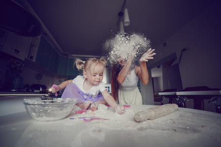 Photo for young beautiful mother teaches daughter prepare dough in the kitchen - Royalty Free Image