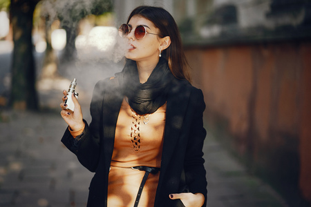 Photo for A stylish girl smoking an e-cigarette - Royalty Free Image