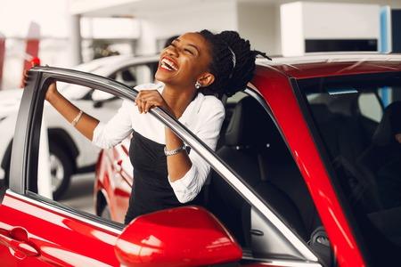 Photo pour Stylish black woman in a car salon - image libre de droit