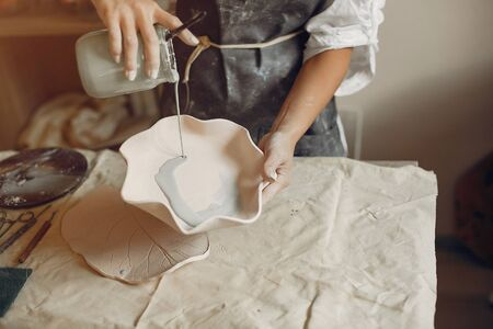 Photo pour Woman in a pottery. Master make a dishes. Artist works with a clay - image libre de droit