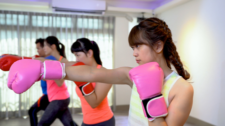 Photo for Fitness women and man training boxing workout at gym. asian people doing professional boxer poses at the class in sports club. group of sporty friends in box gloves doing exercise. - Royalty Free Image