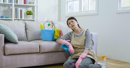 Foto de housewife kneeling down on the wooden floor holding cloth wearing gloves and apron resting. exhausted asian woman tired after doing housework prepared new year holidays. cleaning products in bucket - Imagen libre de derechos