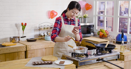 Photo for elegant girl stirring melted chocolate in liquid on stove hot water pot. young woman holding spoon and cellphone taking photo recording down process video of making dessert. handmade valentine gift - Royalty Free Image
