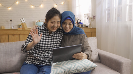 Foto de cheerful Asian best friends in casual clothes using digital tablet for communication with family relatives on sofa. - Imagen libre de derechos