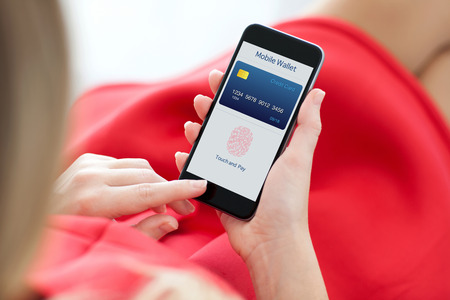 Foto für woman in red dress holding a phone with app mobile wallet and fingerprint for online shopping - Lizenzfreies Bild