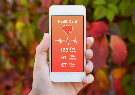 Photo pour female hand holding a white phone with health card on a background of colored leaves - image libre de droit
