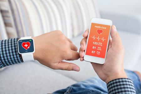 Photo pour male hands holding touch phone and smart watch with mobile app health sensor - image libre de droit