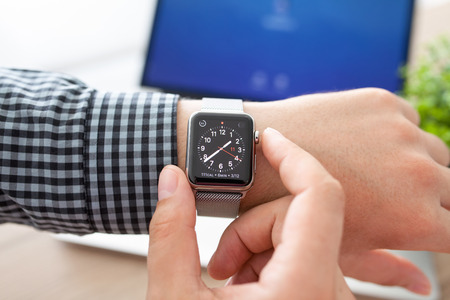 Foto de Alushta, Russia - August 11, 2015: Man hand with Apple Watch and Macbook on the desk. Apple Watch was created and developed by the Apple inc. - Imagen libre de derechos