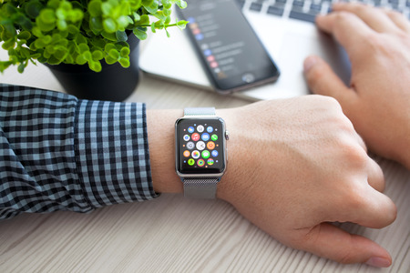 Foto de Alushta, Russia - August 14, 2015: Man hand with Apple Watch and app Icon on the screen. Apple Watch was created and developed by the Apple inc. - Imagen libre de derechos