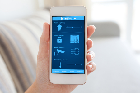 Photo pour female hand holding white phone with smart home on the screen in the room - image libre de droit
