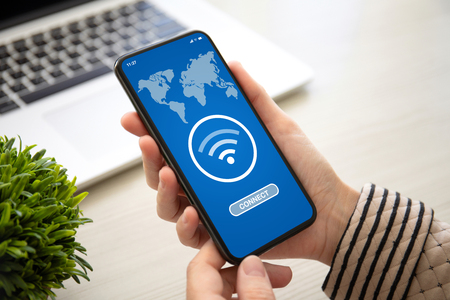 Foto de female hands holding phone with app wifi connect on the screen above the table in the office - Imagen libre de derechos