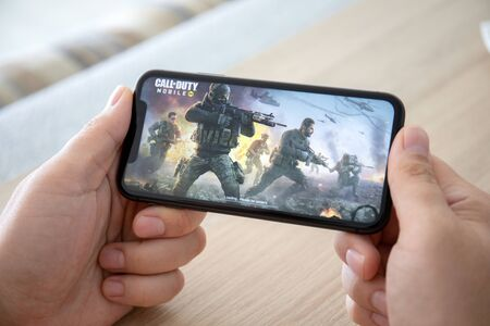 Foto de Anapa, Russia - October 2, 2019: Man hand holding iPhone 11 with game Call of Duty Mobile in the screen. Games Call of Duty was created by the Activision Publishing, inc. - Imagen libre de derechos
