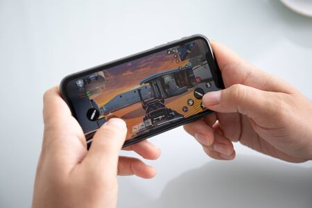 Foto de Anapa, Russia - October 5, 2019: Man hand holding iPhone 11 with game Call of Duty Mobile in the screen. Games Call of Duty was created by the Activision Publishing, inc. - Imagen libre de derechos