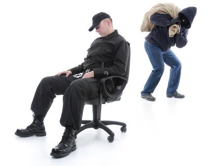 Foto de Security man sleeping on armchair being unaware of masked burglar stealing behind his back - Imagen libre de derechos