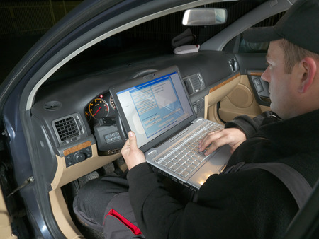 Photo for Auto mechanic checking vehicle identification number of the car using laptop hooked up to the car onboard computer - Royalty Free Image
