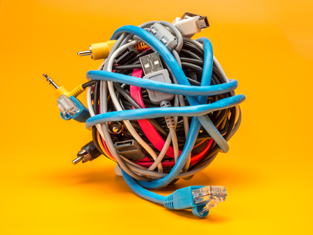 Foto de Tangled roll of computer wires over yellow background - Imagen libre de derechos