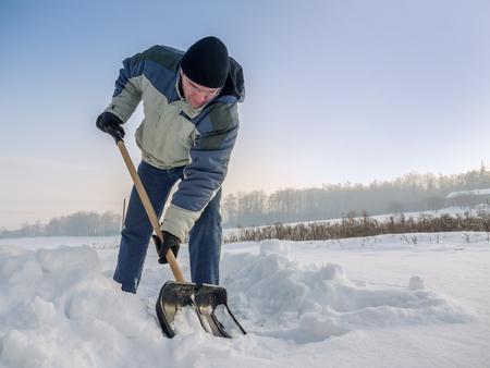 Foto de Man plowing his backyard with shovel after heavy snowing - Imagen libre de derechos