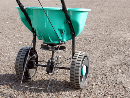 Photo pour Manually operated seeder filled with grass seeds shot on soil - image libre de droit