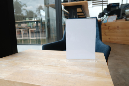 white label in cafe. display stand for acrylic tent card in coffee shop. mockup menu frame on table in bar restaurant. space for text