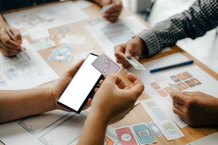 Foto de user experience UX designer designing web on smart phone layout. UI planning mobile application. developer work with business prototype - Imagen libre de derechos