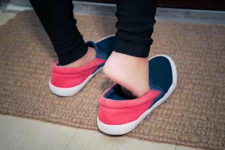 Photo for the young women is wearing the casual shoe before leaving the house - Royalty Free Image