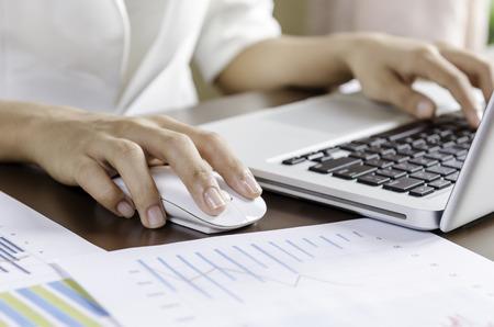 Foto de Woman using a mouse working on the computer - Imagen libre de derechos