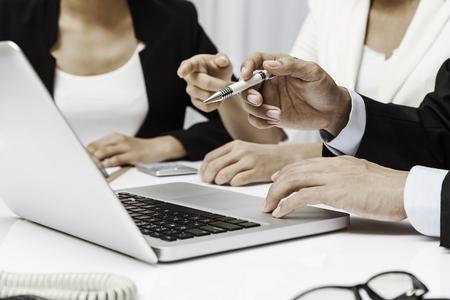 Foto de three business people discussing their work on a laptop - Imagen libre de derechos