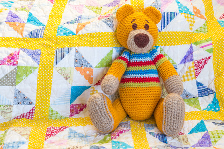 Photo pour orange teddy bear sitting on colourful quilted duvet cover - image libre de droit