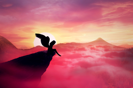 Foto de Silhouette of a lonely fallen angel with long wings standing on a cliff against a paradise sunset. Dusk sky over the clouds in the mountains. Heaven landscape scene screen saver - Imagen libre de derechos