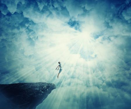Foto de Young boy astral travel, mystical rapture state psychokinesis condition. Magic soul energy show human illusion. Mysterious place into the clouds - Imagen libre de derechos